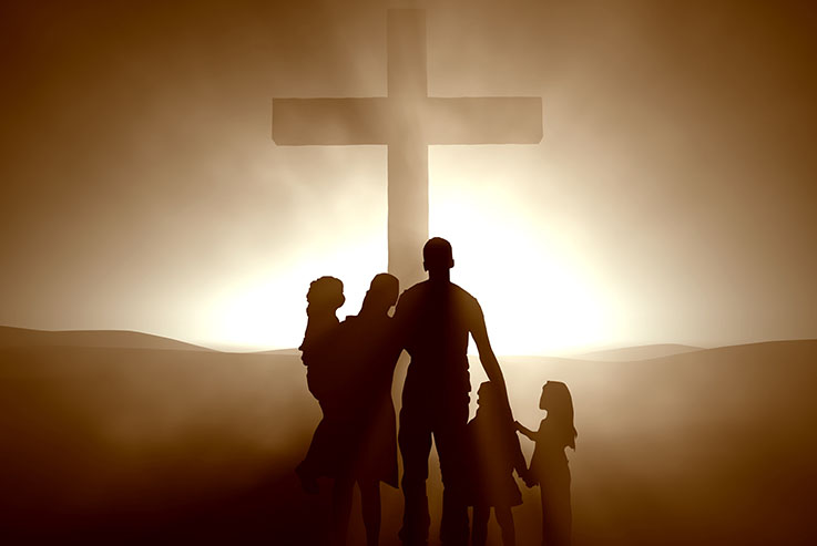 Family of four and large cross silhouhetted against the sun